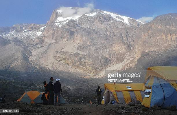 Hikers with tents along a trekking route at Mount Kilimanjaro Tanzania on September 26 2014 Mount Kilimanjaro is a dormant volcanic mountain in...