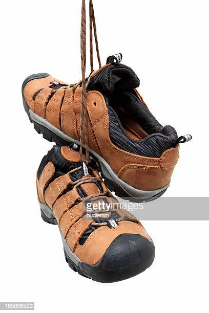 Hiking boots hanging isolated on white background