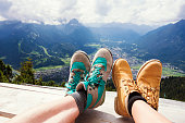 Hiking Boots Relaxing in Front of a Panoramic View – Couple relaxing after their hiking trip to the European Alps on a mountain peak looking down to Garmisch-Partenkirchen, Germany