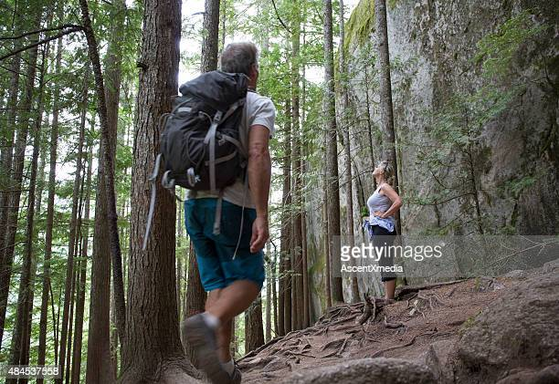 Hiking couple explore forest of hemlock and pine