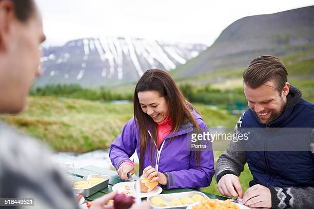 Hiking couple having food against mountains