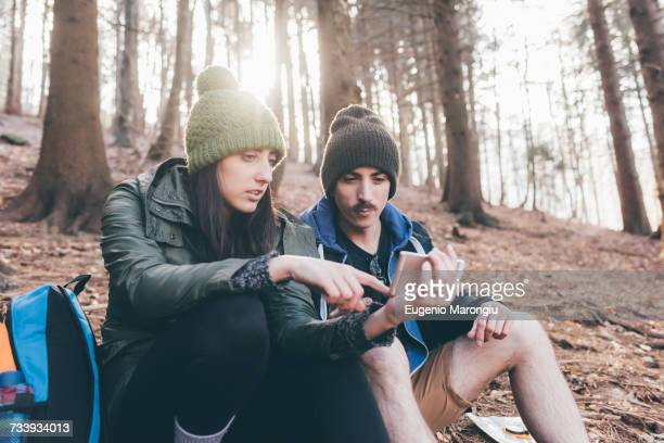 Hiking couple in forest looking at smartphone, Monte San Primo, Italy