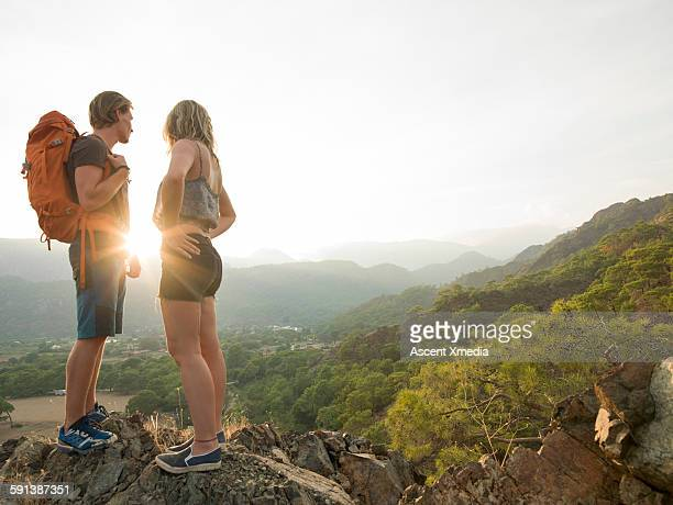 Hiking couple look out over hills, valley, sunrise
