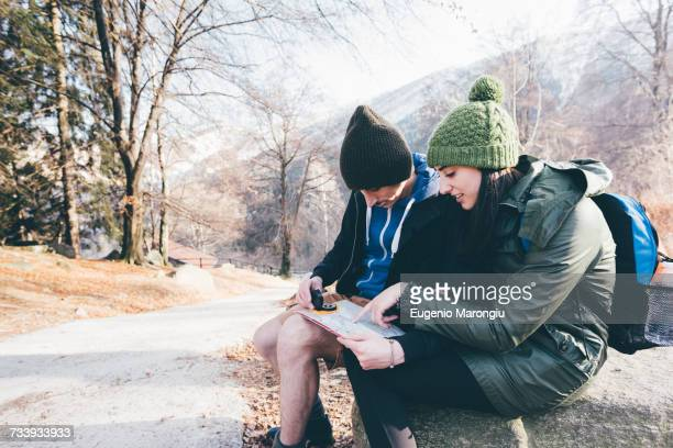 Hiking couple looking at compass and map on roadside, Monte San Primo, Italy
