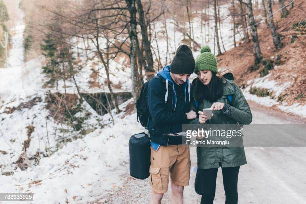 Hiking couple on snowy forest road looking at smartphone, Monte San Primo, Italy