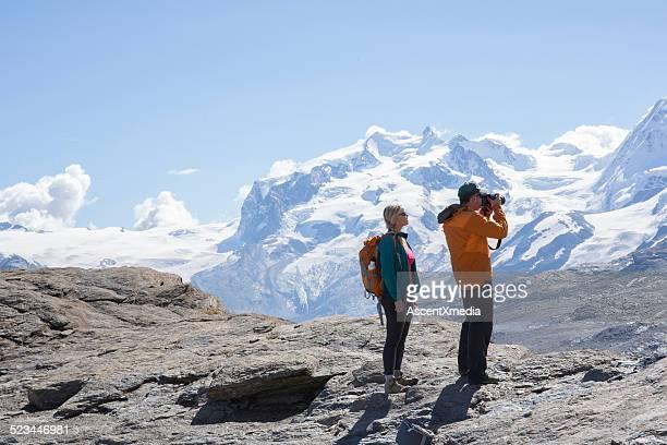 Hiking couple paus on mountain ridge, take picture