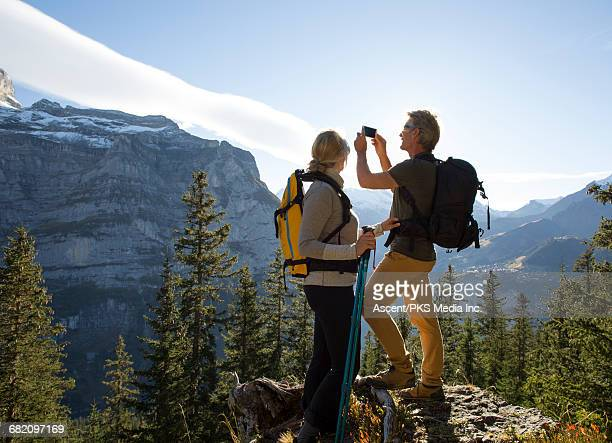 Hiking couple pause on mountain crest, take pic