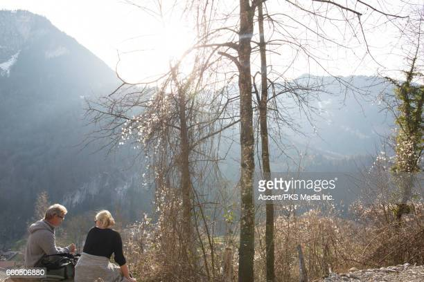 Hiking couple relax on mountain bench, forest
