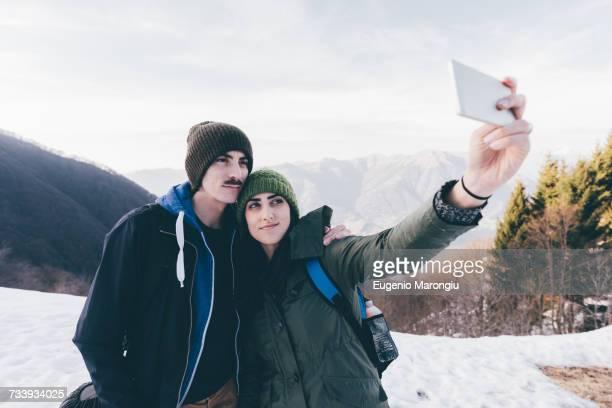 Hiking couple taking selfie in snowy mountains, Monte San Primo, Italy