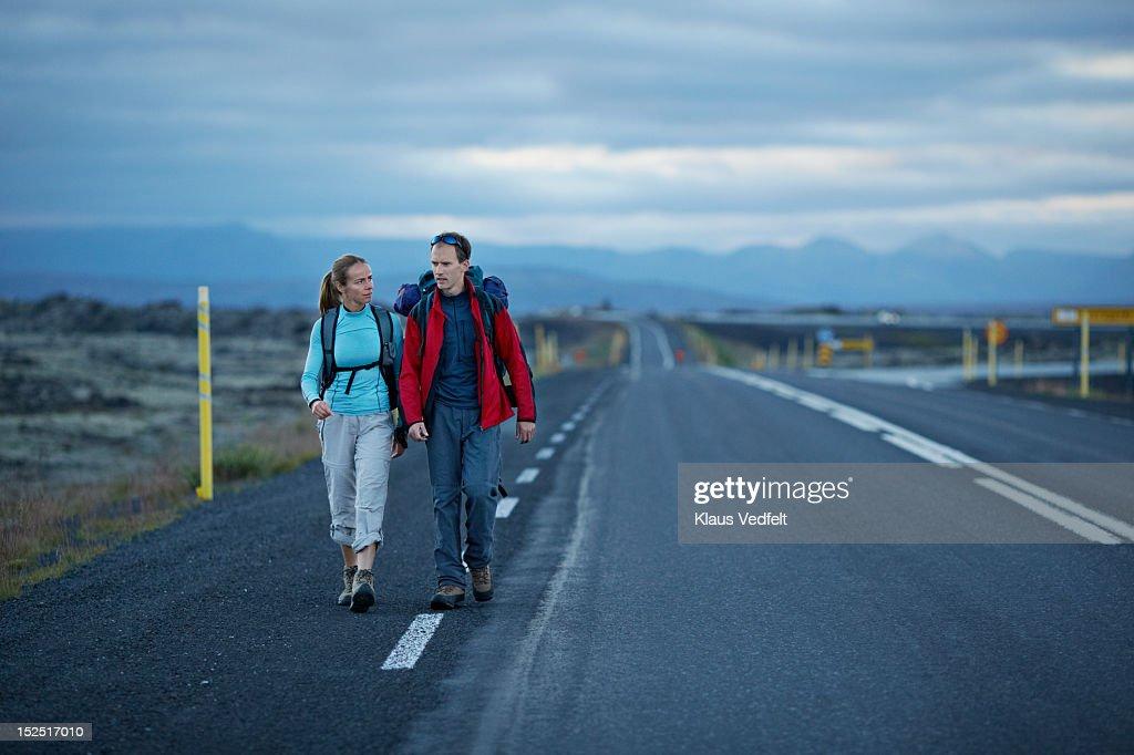 Hiking couple walking alonside long road : Stock Photo