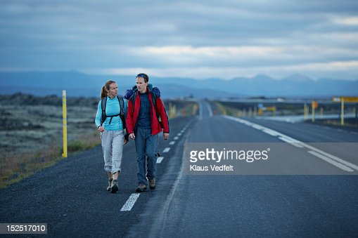 Hiking couple walking alonside long road : Stock Photo
