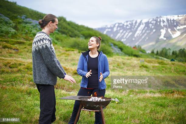 Hiking couple warming hands over grill on mountain