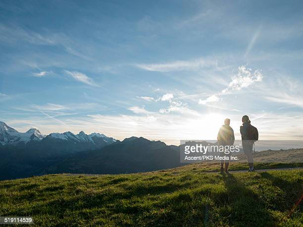 Hiking couple watch sunrise over distant mountains