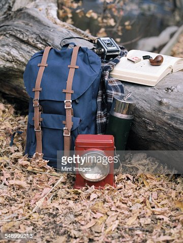 Hiking equipment, a backpack, torch, flask and camera by a tree trunk. A pipe lying on an open book.