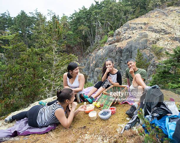 Hiking Family Eating Healthy Vegan Picnic Lunch on Wilderness Mountain