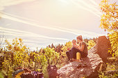 Hiking female friends having snacks on rock