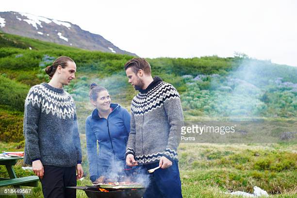 Hiking friends barbecuing food against mountains