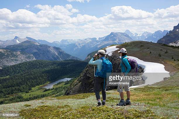 Hiking friends stop to look out to view, mountains