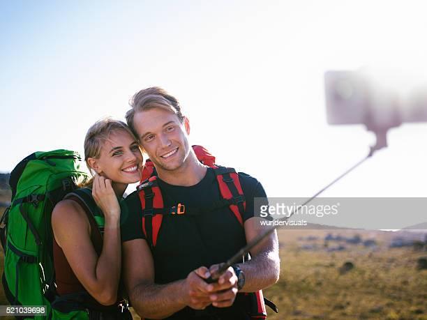 Randonnée homme et femme prenant selfie avec monopode dans la nature