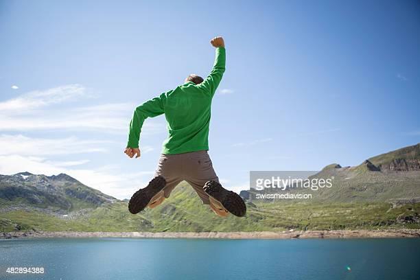 Wandern Mann an der Spitze des Berges springen hoch-Erfolg wird