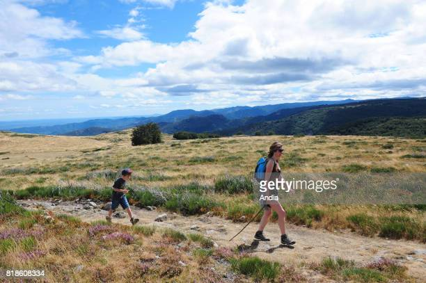 Hiking trail in the Ardeche region Woman and her son walking on a path in the Regional Nature Park of Monts d'Ardeche