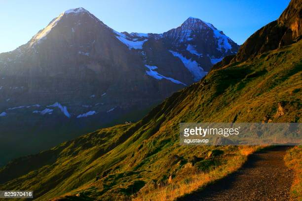 Hiking trail path to Eiger and Monch massif, above idyllic Grindelwald alpine valley and meadows, dramatic swiss snowcapped alps, idyllic countryside, Bernese Oberland,Swiss Alps, Switzerland
