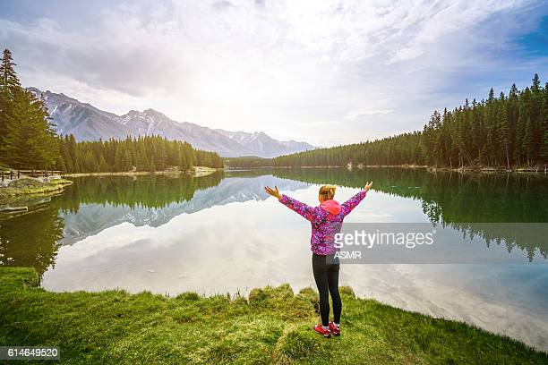 Hiking woman arms open to nature view