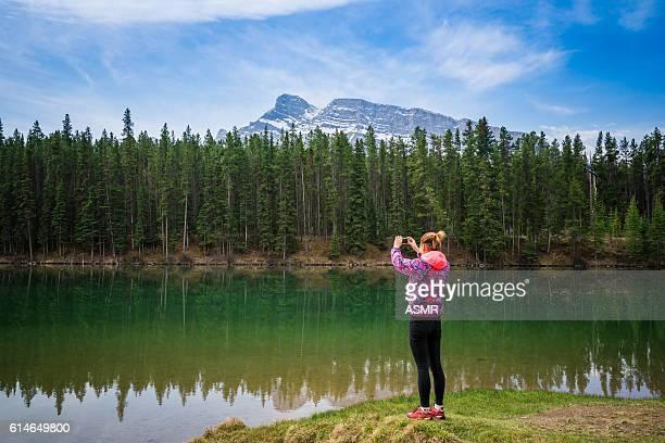 Hiking woman use smart phone taking photo