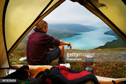 Hiking young man and scenic view of lake Gjende Jotunheimen