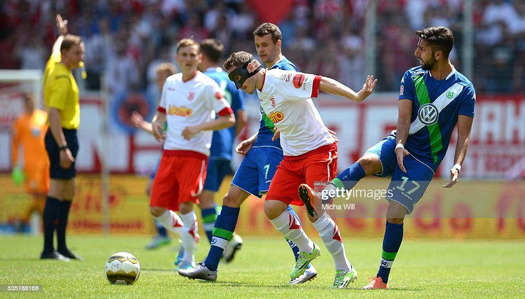 Hilal El-Helwe (from R) of Wolfsburg, Andreas Geipl of Regensburg and Robert Herrmann of Wolfsburg compete for the ball during the Third League play off second leg match between Jahn Regensburg and VfL Wolfsburg II at Continental Arena on May 29, 2016 in Regensburg, Germany.