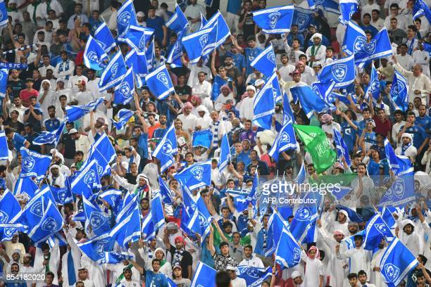 A Hilal's supporter waves their flags ahead the first leg of their AFC Champions League semifinal football match against Persepolis at the Mohammed...