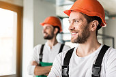 Happy laughing builders are standing at quarters and looking aside with smile. They wearing orange helmet. Portrait