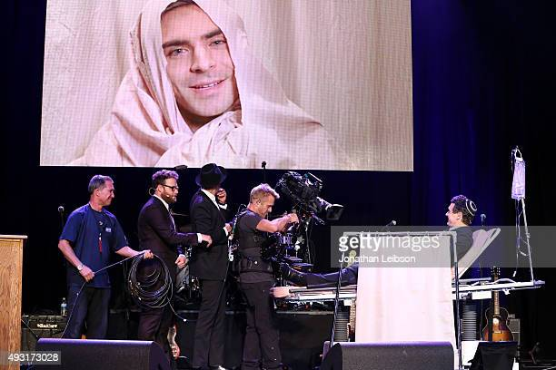 Hilarity for Charity cofounder/show host Seth Rogen actor Jeff Goldblum actor James Franco perform onstage as a video of actor Zac Efron plays on a...