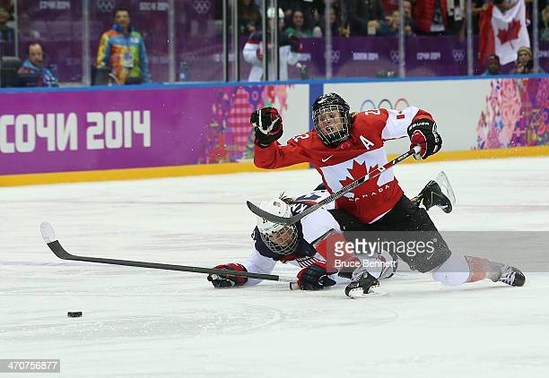 Hilary Knight of the United States and Hayley Wickenheiser of Canada dive for the puck during the Ice Hockey Women's Gold Medal Game on day 13 of the...