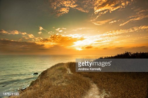 Hill path at sunset by Ocean : Stock Photo