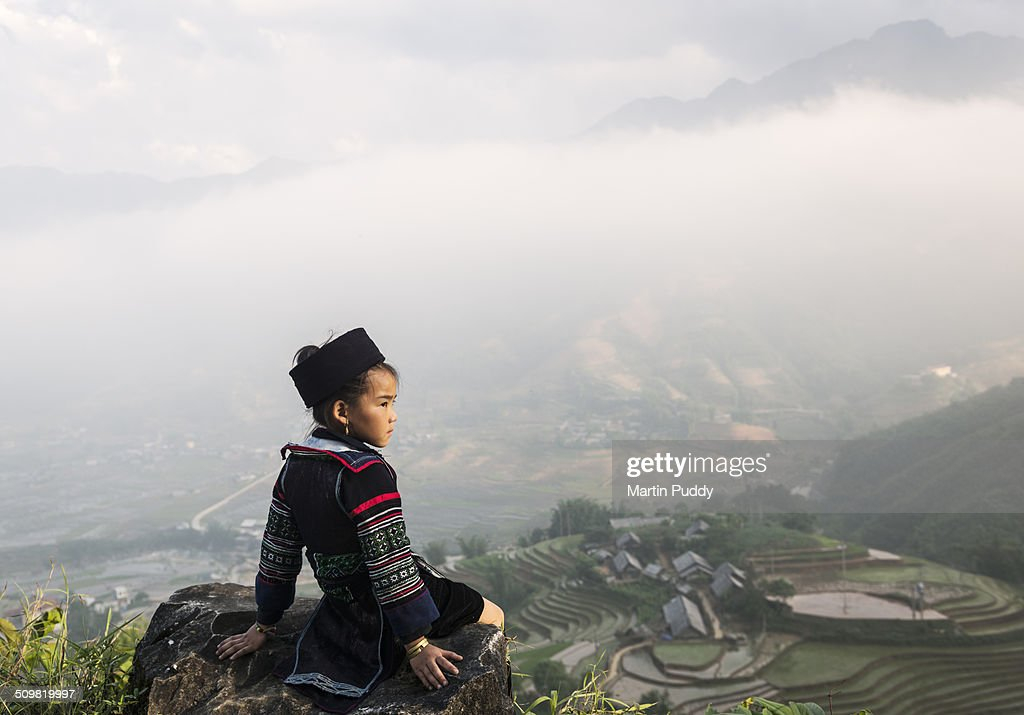 Hill tribe girl sitting on hill side above valley