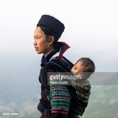 Hill tribe woman carrying baby on back