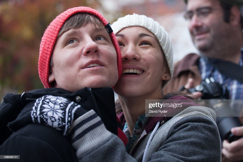 Hill Wolfe and Ili Wong watch the festivities as newlyweds exit City Hall on December 9, 2012 in Seattle, Washington. Today is the first day that same-sex couples can legally wed in Washington state.