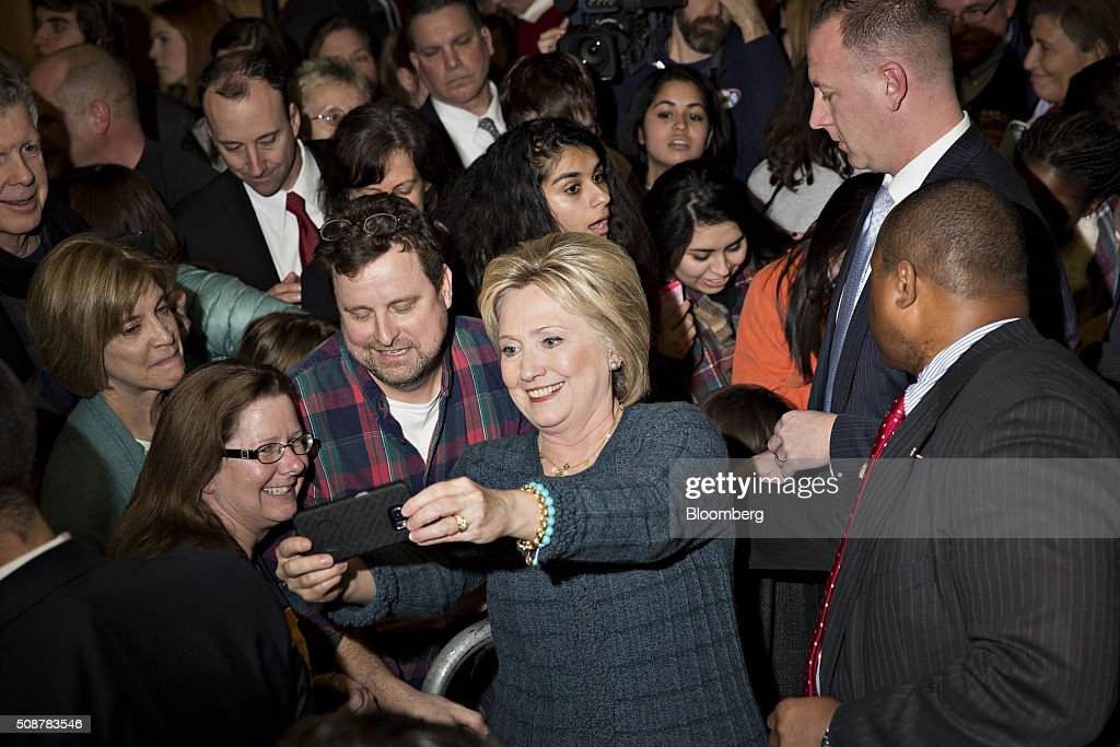 Hillary Clinton, former Secretary of State and 2016 Democratic presidential candidate, center, stands for a selfie photograph with attendees during a campaign event in Concord, New Hampshire, U.S., on Saturday, Feb. 6, 2016. Trailing Bernie Sanders in the Democratic contest by 20 percentage points or more in some polls of voters in the state, Clinton recalled that New Hampshire gave her a come-from-behind victory in the 2008 primary race and a dramatic boost to her husband, Bill Clinton, in his first run for the presidency in 1992. Photographer: Daniel Acker/Bloomberg via Getty Images