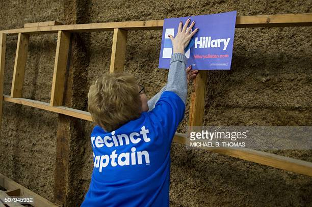 A Hillary Clinton Precinct Captain hangs a poster at a Democratic Party Caucus at Jackson Township Fire Station on February 1 2016 in Keokuk Iowa Ted...