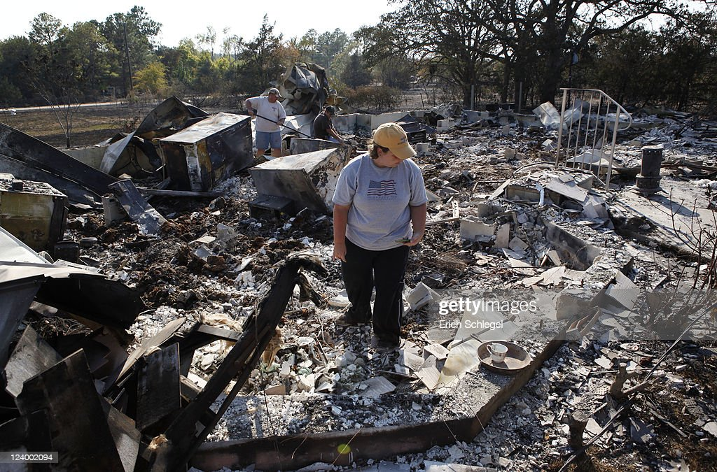 Hillary Polly looks through the family belongings as Thomas Polly tries to pry open a fireproof gun safe with his father Louie Polly in the background amongst the rubble of their burned house in a subdivision, September 7, 2011 near Bastrop, Texas. Several large wildfires have been devastating Bastrop County for the last three days, but are now 30 percent contained, according to the Texas Forest Service.