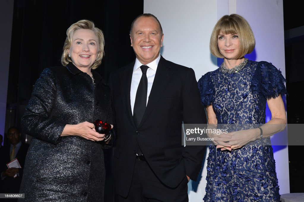 Hillary Rodham Clinton, recipient of the <a gi-track='captionPersonalityLinkClicked' href=/galleries/search?phrase=Michael+Kors+-+Fashion+Designer&family=editorial&specificpeople=4289231 ng-click='$event.stopPropagation()'>Michael Kors</a> Award for Outstanding Community Service, Designer <a gi-track='captionPersonalityLinkClicked' href=/galleries/search?phrase=Michael+Kors+-+Fashion+Designer&family=editorial&specificpeople=4289231 ng-click='$event.stopPropagation()'>Michael Kors</a>, and Vogue editor-in-chief <a gi-track='captionPersonalityLinkClicked' href=/galleries/search?phrase=Anna+Wintour&family=editorial&specificpeople=202210 ng-click='$event.stopPropagation()'>Anna Wintour</a> pose on stage at the God's Love We Deliver 2013 Golden Heart Awards Celebration at Spring Studios on October 16, 2013 in New York City.
