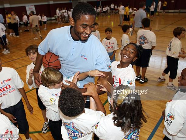 Hilton Armstrong center for the New Orleans Hornets works with campers on a basketball drill at the unveiling of the New Orleans AllStar logo at the...