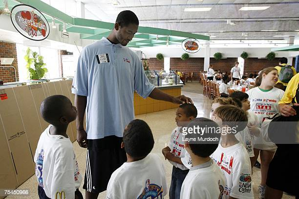 Hilton Armstrong center for the New Orleans Hornetsworks with campers as he unveils the New Orleans AllStar logo at the Jr NBA/Jr WNBA Basketball...