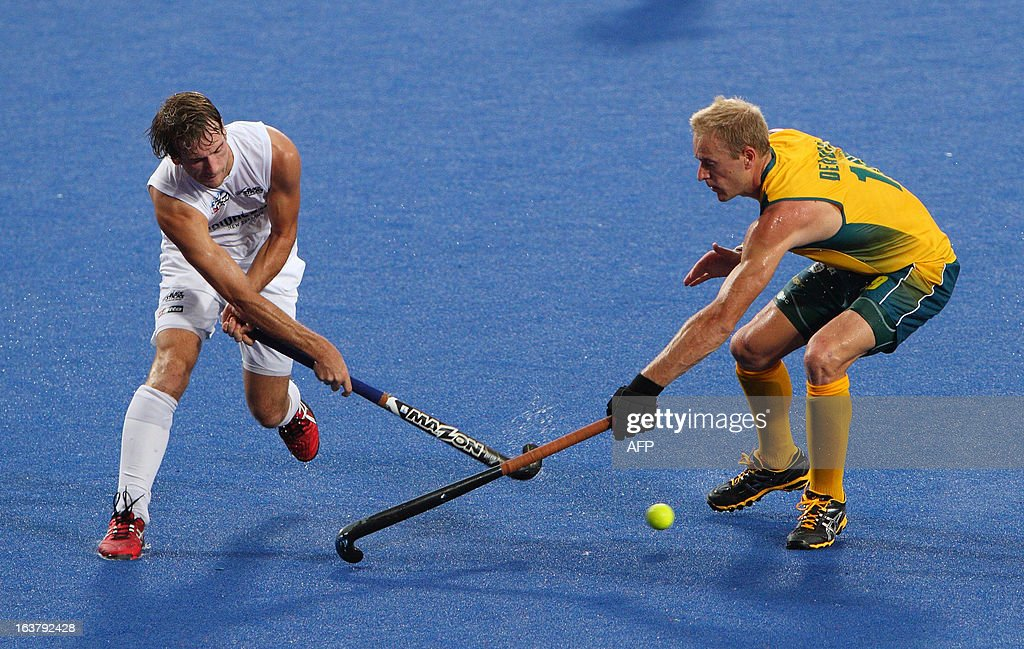 Hilton Bllair of New Zealand tries to hit the ball pass Shaw Alex of Australia during their match at the Sultan Azlan Shah Cup men's field hockey...