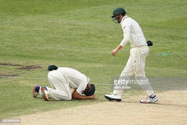 Hilton Cartwright of Australia lies on the ground as Matt Renshaw of Australia watches on after Cartwright was hit while fielding during day three of...