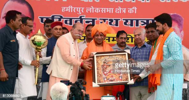 Himachal BJP leaders felicitate UP Chief Minister Yogi Adityanath by offering a bludgeon at closing of Himachal BJP's Parivartan Rath Yatra at Amb on...
