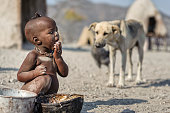 Himba child eating from a rusty pot