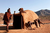 A Himba family in front of their home in the village located close to the Kunene river in Namibia