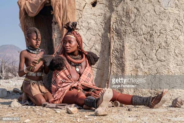 Himba girl combing the hair of one of her relatives Himbas are a bantu tribe who migrated into what today is Namibia a few centuries ago They...